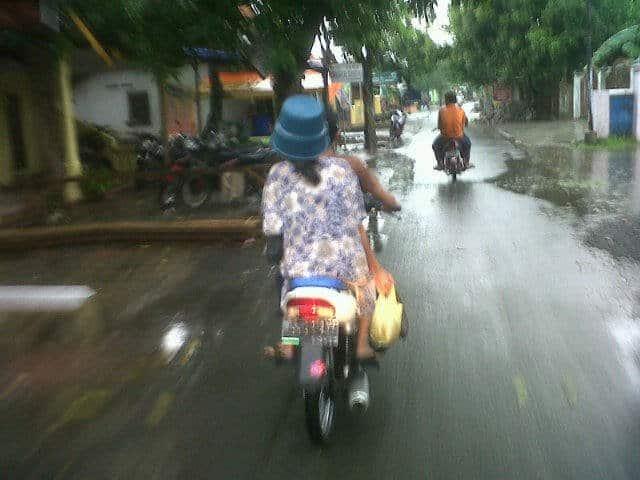 Hujan-hujan kayak gini paling enak beli makanan hangat. Tapi lupa tuh si ibunya bawa helm, langsung aja deh pakai timba kecil.