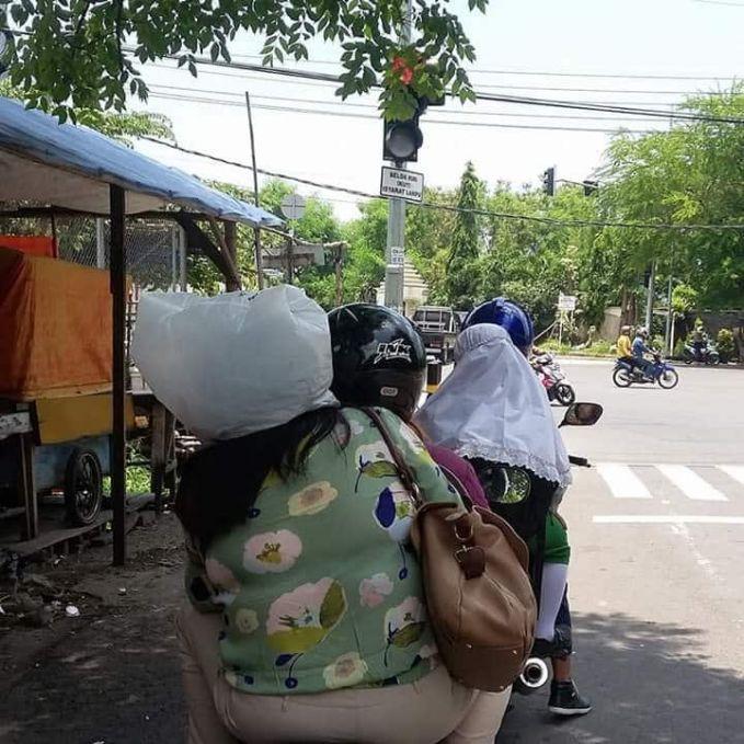 Nggak panas apa pakai tas kresek buat dijadiin helm di tengah terik matahari kayak gitu Bu?.