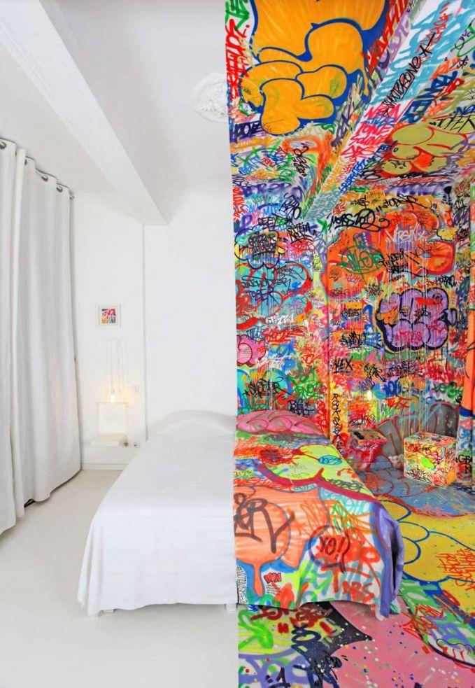 Seniman asal Prancis mendekorasi kamar hotelnya menjadi dua seperti ini. Satu putih polos, dan sisi setelahnya full grafity.