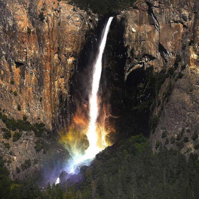 Seperti di negeri dongeng, air terjun ini menyatu dengan pelangi sehingga seperti ada luapan api di bawahnya.
