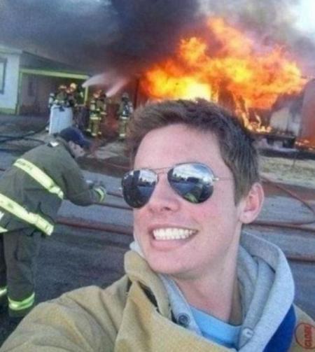 Bukannya mengevakuasi korban, pria ini malah berselfie dengan latar belakang rumah kebakaran.