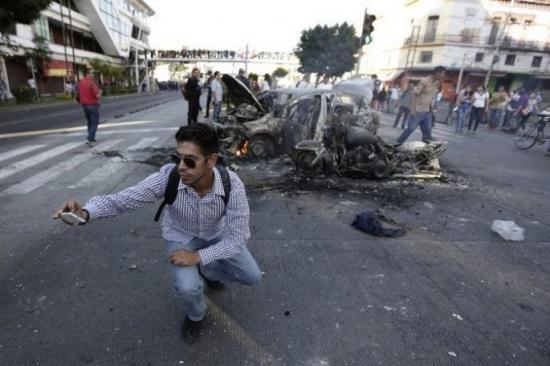 Bedanya dengan yang atas, pria ini dengan asiknya berselfie dengan kendaraan yang habis kecelakaan dan terbakar.