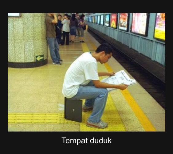 Dengan santainya sambil baca koran, pria tersebut menjadikan laptop sebagai tempat duduk saat menunggu kereta.