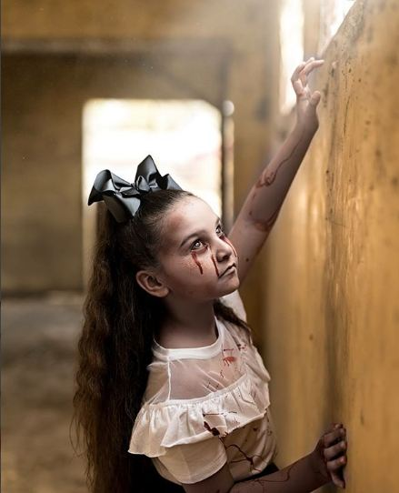 Anak gadis ini terlihat sedih sambil menatap cahaya dari jendela. Dia juga menangis dan mengeluarkan air matan darah.