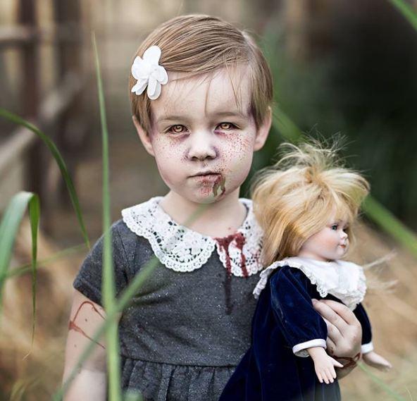 Bukan cuma wajahnya aja yang menyeramkan, boneka yang dibawa juga menambah kesan seram dari foto ini.