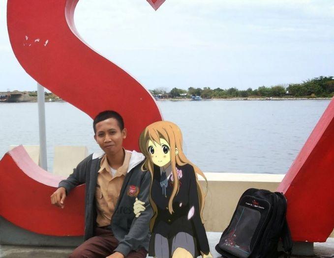 Oh, ternyata si otong dan cewek animenya lagi pacaran di pinggir danau. Romantis banget ya mereka berdua.