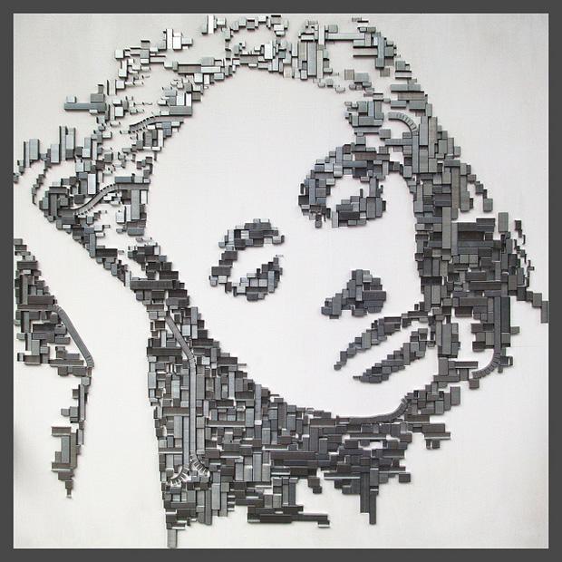 Kumpulan staples dari berbagai macam ukuran yang disatukan jadi mozaik wajah seorang wanita.