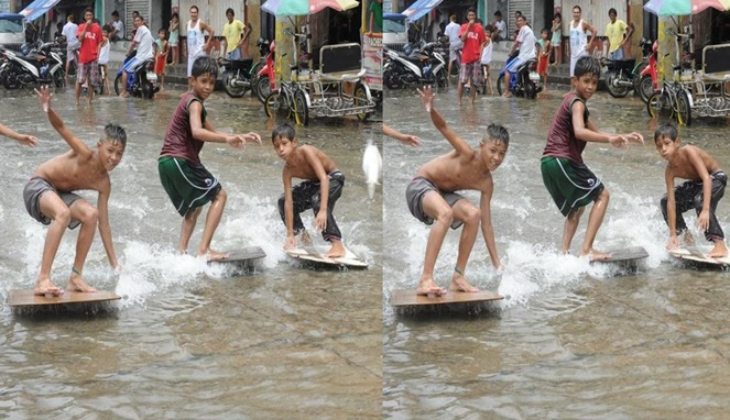 Nggak mau kalah dari yang tadi, anak-anak ini juga berselancar dengan menggunakan triplek dia atas banjir.