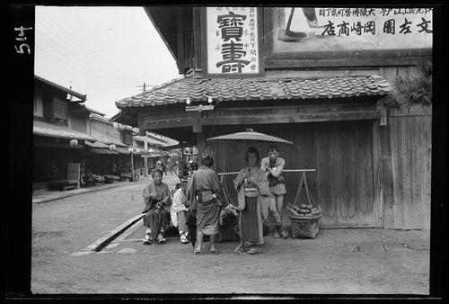 Suasana sudut jalan perkampungan di Jepang yang masih tradisional. Dalam foto nampak sekelompok wanita dan pedagang keliling menjajakan barang dengan cara dipikul.