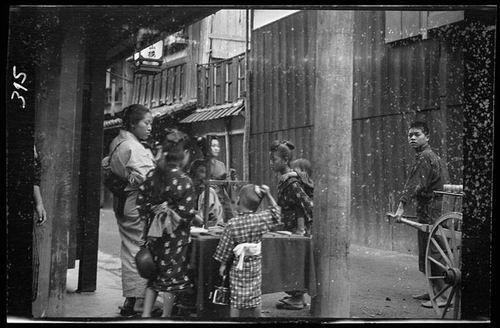 Anak-anak mengerumuni salah satu pedagang di sebuah pasar. Mungkin pedagang tersebut mejual makanan atau benda yang menarik bagi anak-anak.