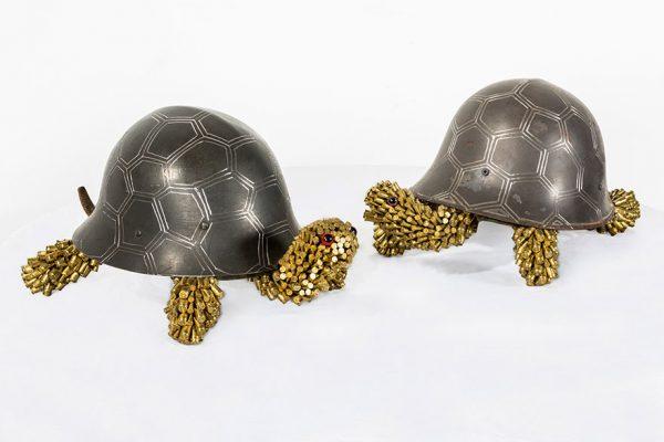 Badan dan cangkang kura-kuranya sama-sama terbuat dari perlengkapan militer gaes, ada helm baja dan selongsong peluru.