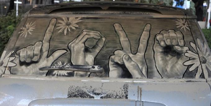 Pesan damai dan cinta bisa datang dari mana saja lewat media apa saja. Termasuk melalui lukisan di kaca mobil kotor.