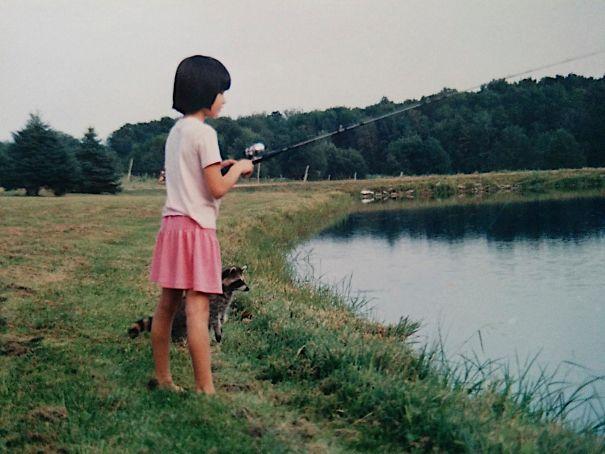 Foto anak yang lagi mancing ditemani rakun peliharaannya ini diambil pada sekitar tahun 1980-an.