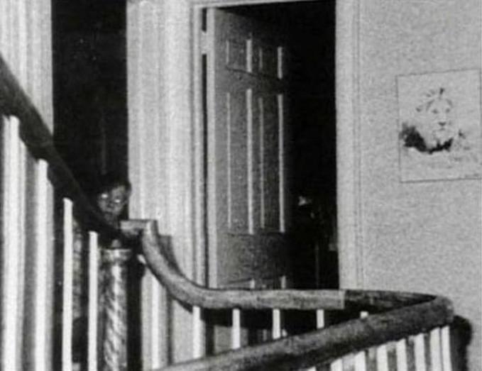 Dibalik pintu terlihat anak kecil yang melihat kearah kamera dengan mata bercahaya.