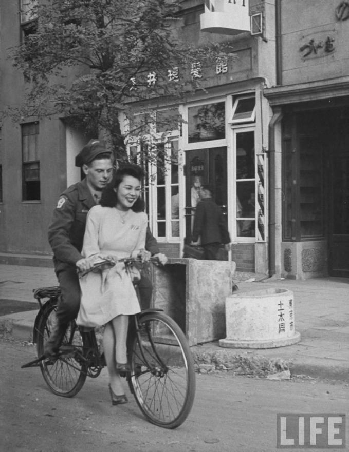 Tentara Amerika Serikat nampak sedang mengajak gadis Jepang untuk berjalan-jalan menyusuri kota di tahun 1946.