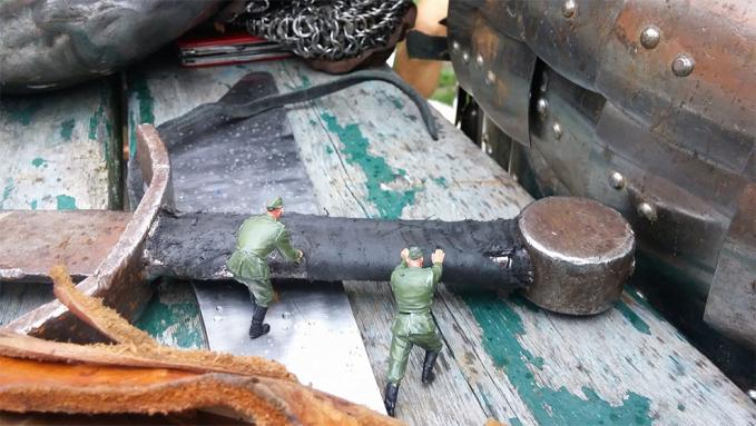 Keduanya nampak bersusah payah mendorong besi gagang pedang. Lumayan berat juga lho.