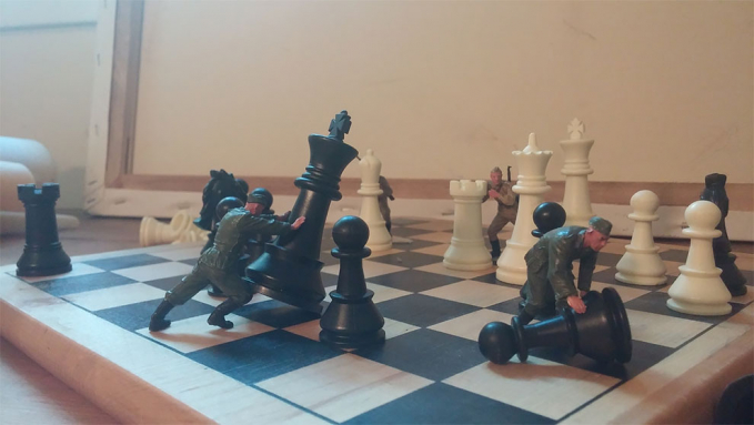 Menata pion-pion catur yang berserakan.