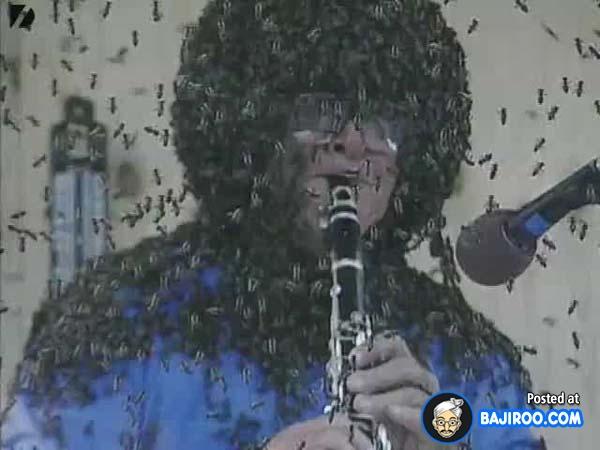 Skill tingkat dewa deh pria satu ini. Walau dikerubutin ribuan lebah masih sempat-sempatnya main musik.