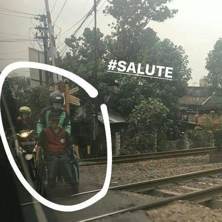 Seorang ojek online menuai pujian karena kebaikannya menyeberangkan orang melewati rel kereta api.