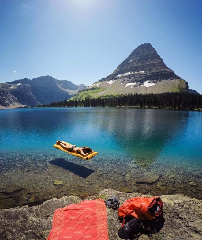 Saking beningnya, wanita yang sedang berjemur di atas danau ini terlihat seperti melayang dengan karpet terbang.
