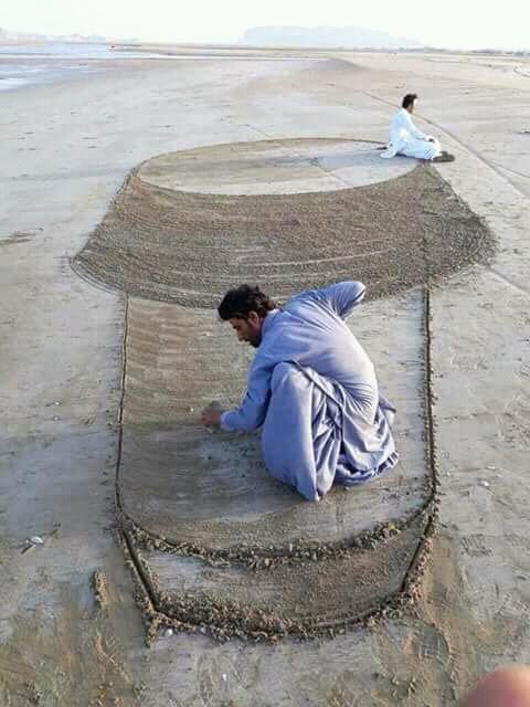 Duduk di atas sebuah gundukan pasir.