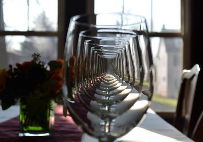 Foto ilusi optik yang tercipta dari kumpulan gelas wine yang diletakkan berjejer di meja. Hasilnya seperti lorong-lorong kaca.