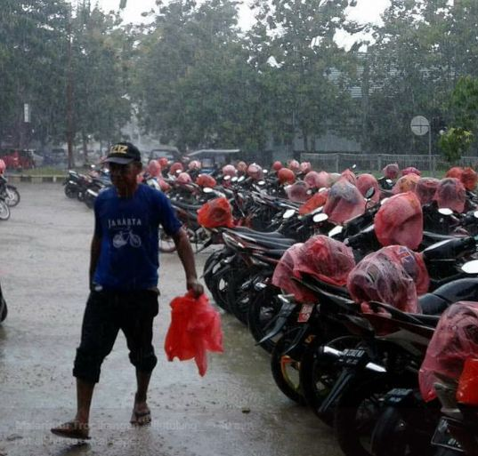 Beberapa waktu lalu, foto ini sempat menjadi viral di media sosial. Yaitu tukang parkir yang menutup helm yang ada di parkiran motor dengan kresek merah. Tulus banget kan? Mungkin cuma di Indonesia kamu menemukan kebaikan seperti ini.