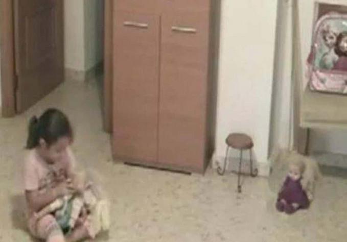 Seorang anak terlihat bermain boneka dan ada boneka lainnya yang sedang duduk menemani.