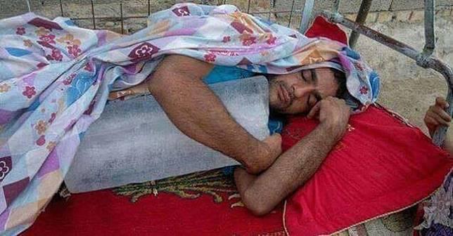 Saking panasnya suhu, pria ini memilih es balok sebagai guling untuk menemaninya tidur siang.