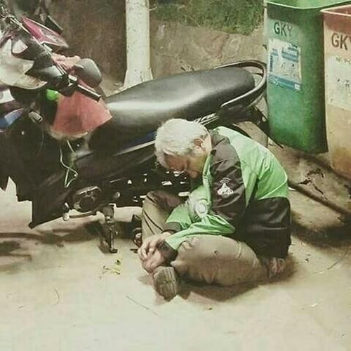 Mungkin terlalu lelah menunggu pelanggan, bapak ojol ini ketiduran di samping motornya.