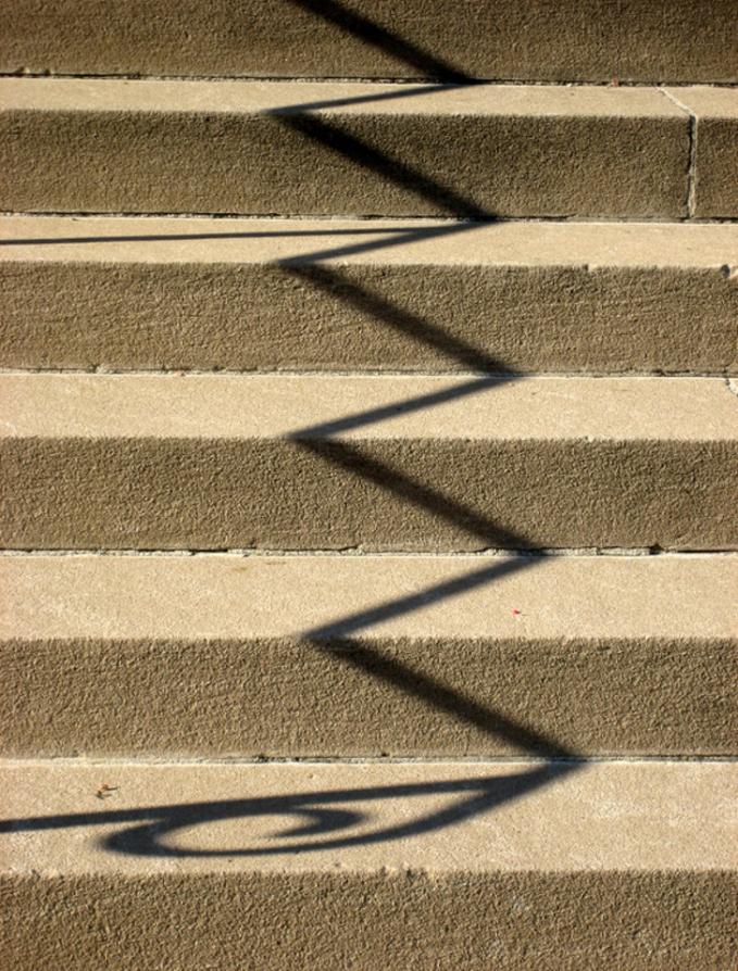 Bayangan pagar zigzag mengikuti alur anak tangga.