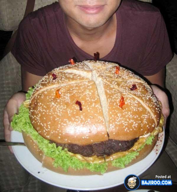 Ulang tahun dikasih kue tart sudah biasa, tapi coba deh sesekali diganti pakai burger jumbo kayak gini. Gimana Pulsker, kalau kalian sanggup nggak nih ngabisin burgernya sendirian? (Sumber : Bajiroo.com)
