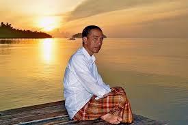 Momen saat fajar pertama tahun 2016 Fotografer istana mendokumentasi Jokowi saat menikmati fajar pertama di tahun 2016 dengan duduk di dermaga dan mengenakan baju putih lengan panjang, sarung, dan tanpa beralaskan kaki.