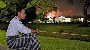 Momen menikmati meriahnya kembang api di Istana Bogor. Saat pergantian tahun 2017 Jokowi menikmati meriahnya kembang api di taman Istana Bogor dengan mengenakan sarung kotak - kotak dan baju lengan panjang.