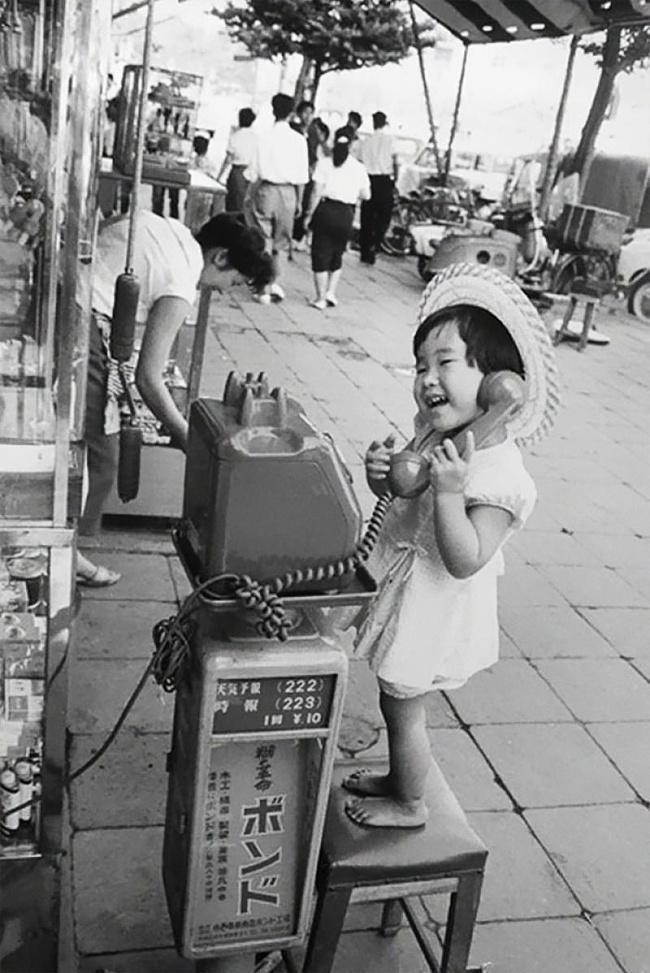 Adek kecil ini mencoba menggunakan telepon umum di Jepang tahun 1958.
