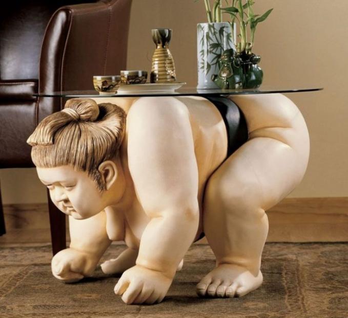 Meja berbentuk Sumo cilik lagi menahan beban berat di punggungnya cocok dipajang di ruang tamu.
