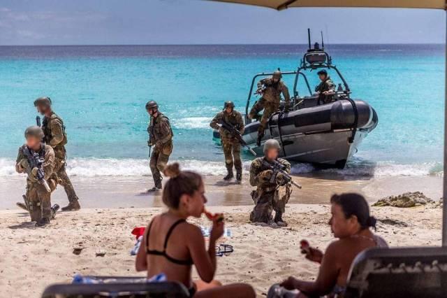 Ada latihan perang bukan malah menyingkir malah asyik ngobrol di pinggir pantai.