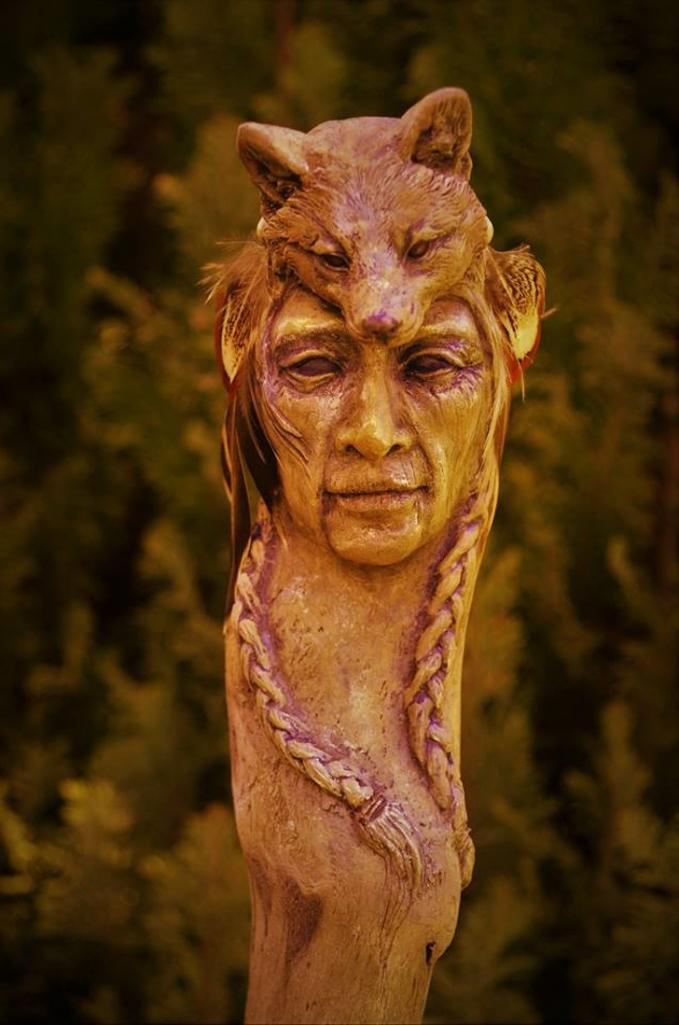 Pahatan wajah seseorang dengan seekor rubah di kepalanya sampai guratan-guratan wajahnya terlihat detail.