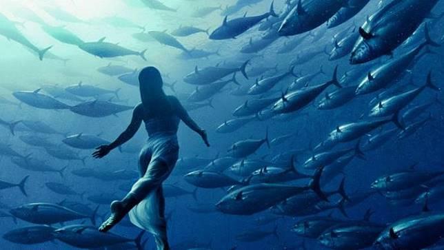 Seorang model yang berenang dilautan bersama kumpulan ikan.