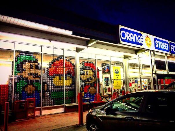 Susunan kardus dan kaleng ditata sedemikian rupa membentuk sebuah gambar Mario Bros.