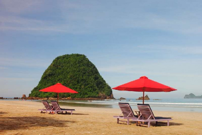 Pantai Pulau Merah Banyuwangi, Jawa Timur Pantai Pulau Merah terletak di kecamatan Pasanggaran di Banyuwangi. Menggunakan banyak payung warna merah pantai ini juga punya pemandangan indah yang tak terkalahkan. Ada bukit hijau tak jauh dari pantai yang bisa kamu kunjungi saat airnya surut. Pemandangan sunset di pantain ini juga luar biasa.