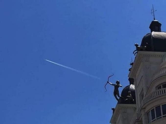 Pesawat yang lewat pas banget di atas patung dan seolah nampak seperti anak panah yang dilepas.