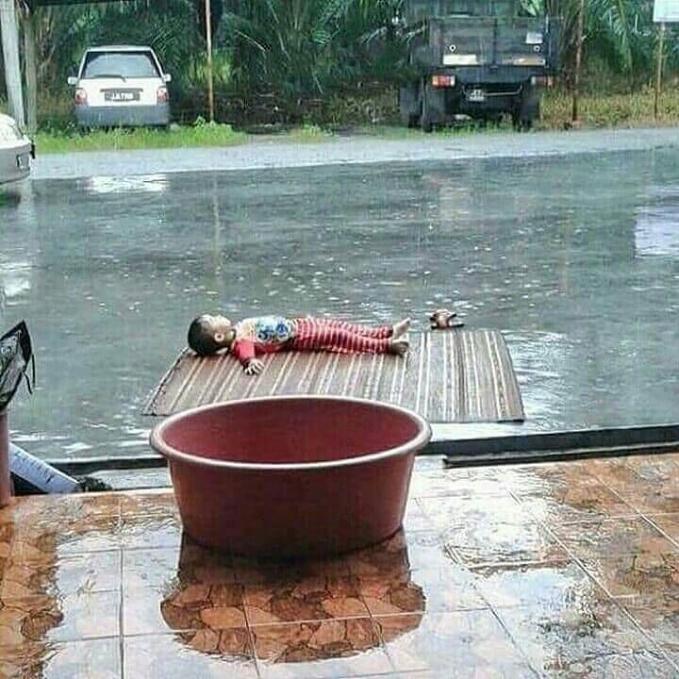 Duh dek, nggak bahaya tuh mandi hujan di tengah jalan?