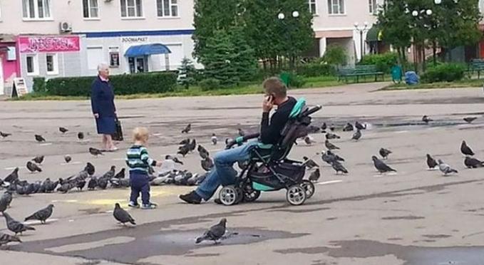 Santai banget pak, duduk di stroller anaknya.