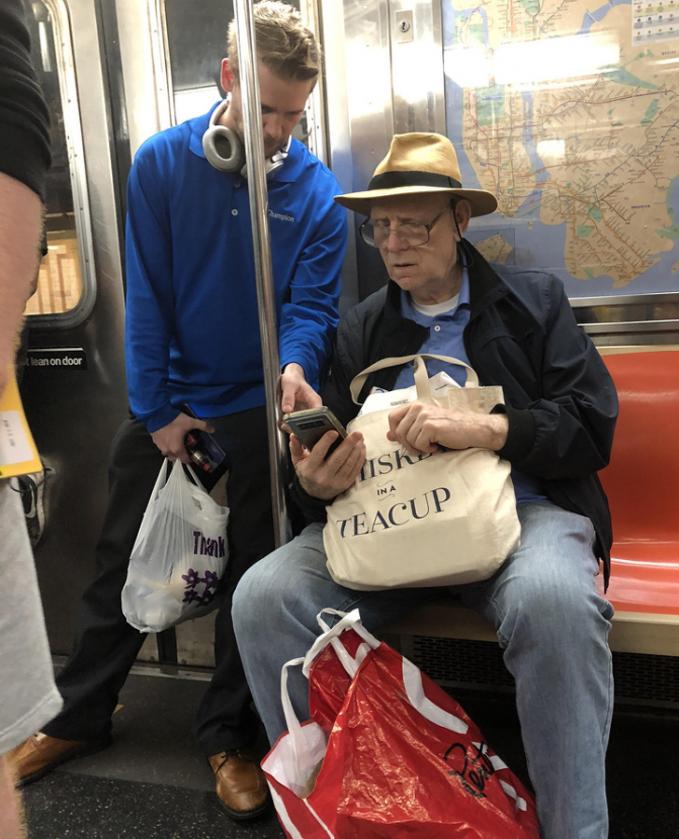 Seorang pria lanjut usia ditolong oleh pemuda saat dia tidak mengerti apa yang ada di smartphonnya.