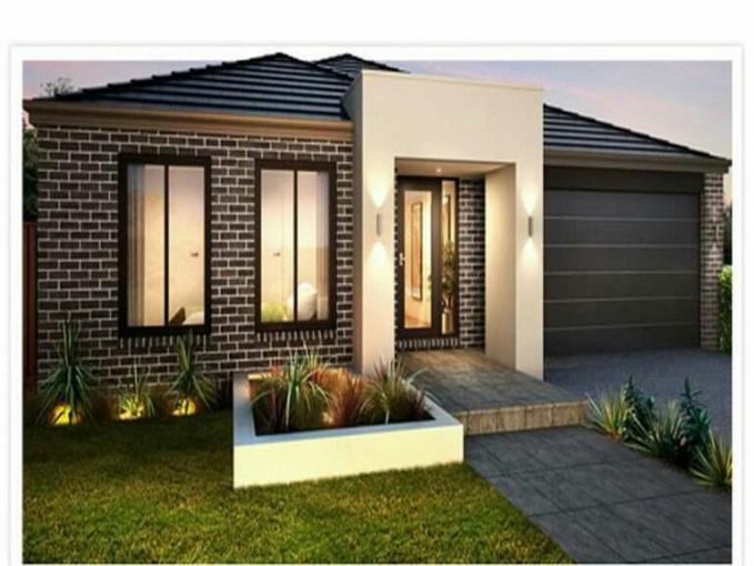 Rumah kecil dengan halaman yang hijau dan lumayan luas dn corak rumah yang dipilih batu batu bata dan dengan bunga bunga di pekarangan rumah.