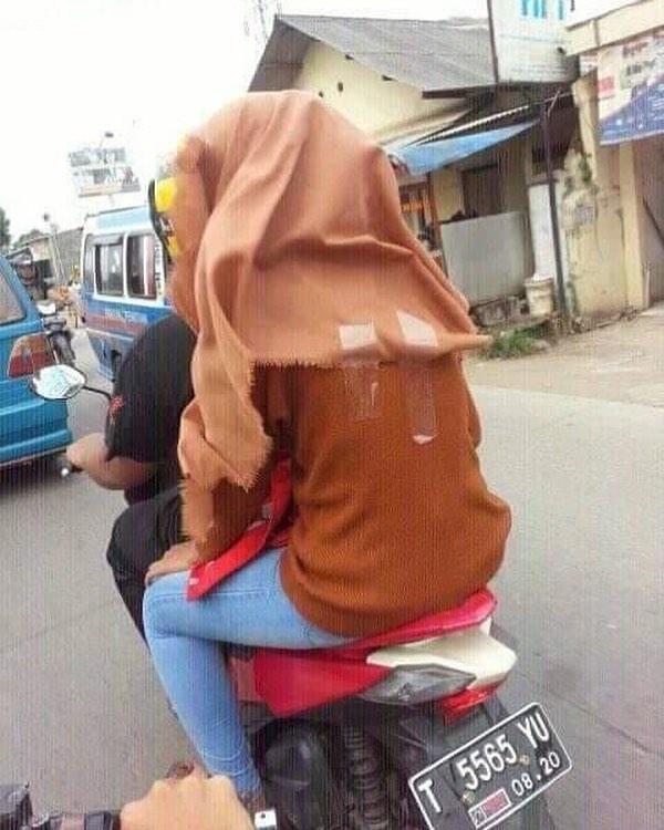 Kamu bisa meniru cara ini agar jilbabmu nggak terbang-terbang saat naik motor.