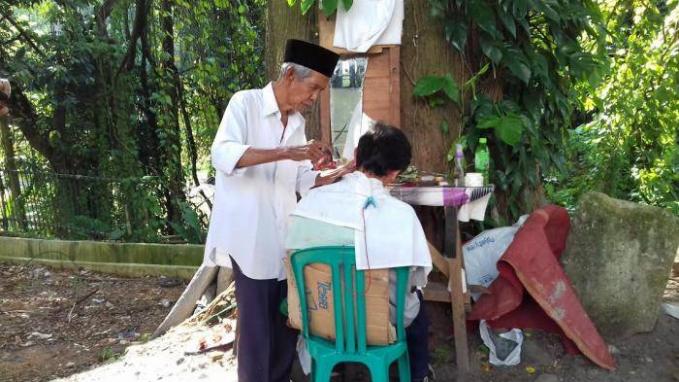 Dulu tukang cukur keliling ini disebut tukang cukur DPR. Tapi bukan anggota dewan lho Pulsker, melainkan Dibawah Pohon Rindang. Jadi nyukurnya berasa sejuk kalau dibawah pohon.