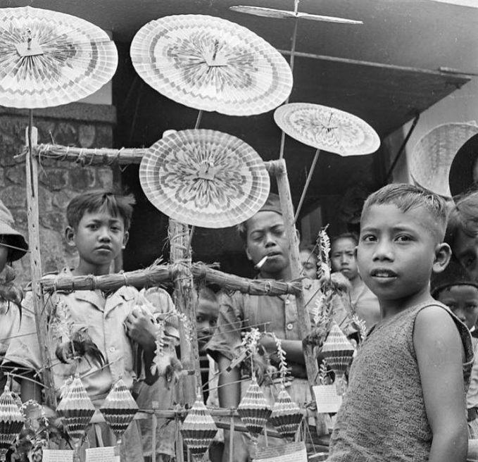 Mainan tradisional kipas dan payung dari kertas seperti ini dulu adalah mainan favorit bagi anak-anak Indonesia. Nampak, anak-anak ini sedang mengerumuni penjual mainan tradisional.