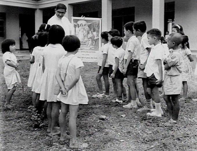 Dengan rasa penasaran akan ilmu yang baru, anak-anak di sekolah Katholik Nusa Tenggara Timur ini mendengarkan penjelasan guru mereka. Foto tersebut diambil tahun 1965 gaes.